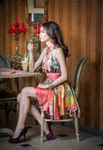 Fashionable attractive woman in multicolored dress sitting in restaurant. Beautiful brunette posing in elegant vintage scenery with a juice glass. Attractive female drinking lemonade in cafeteria — Stock Photo