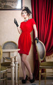 Beautiful woman in red with gloves and creative hairstyle posing near long purple  curtains. Romantic mysterious lady smoking in luxurious vintage interior. Attractive fashionable female in red. — Stock Photo