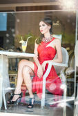 Fashionable attractive young woman in red dress sitting in restaurant, beyond the windows. Beautiful brunette posing in elegant vintage scenery with a lemonade glass. Photo concept through the window — Foto de Stock
