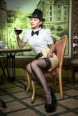 Fashionable attractive young woman with male outfit, bow and black stockings sitting in restaurant. Beautiful lady posing in elegant vintage scenery with a glass of wine. Female in luxurious interior — Stock Photo