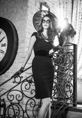 Young beautiful brunette woman in black standing on stairs near an over sized wall clock. Elegant romantic mysterious lady with movie star look in luxurious vintage interior, black and white photo. — Foto de Stock
