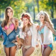 Three sexy women with provocative outfits putting clothes to dry in sun. Sensual young females laughing putting out the washing to dry in sunny day. Perfect body housewives with a dog, shot in forest — Stock Photo #51301623