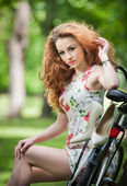 Beautiful girl wearing a nice short dress having fun in park with bicycle. Pretty long hair woman with romantic look resting on her bike in a sunny day. Gorgeous curly female relaxing smiling outdoor. — Stock Photo