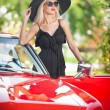 Outdoor summer portrait of stylish blonde vintage woman posing near red retro car. fashionable attractive fair hair female with black hat near a red vehicle. Sunny bright colors, outdoors shot. — Foto de Stock   #51385433