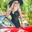 Outdoor summer portrait of stylish blonde vintage woman posing near red retro car. fashionable attractive fair hair female with black hat near a red vehicle. Sunny bright colors, outdoors shot. — Foto de Stock   #51385435