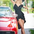 Summer portrait of stylish blonde vintage woman with long legs posing near red retro car. fashionable attractive fair hair female with black hat near a red vehicle. Sunny bright colors, outdoors shot. — Stockfoto