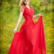 Portrait of young beautiful blonde woman wearing a long red elegant dress posing in a green meadow. Fashionable sexy attractive girl with blue eyes in field. Gorgeous fair hair female, outdoor shot. — Stock Photo #51419555
