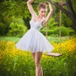 Attractive girl in white short dress posing near a tree swing with a flowery meadow in background. Blonde young woman with ballerina dress under a tree in a ballet position during a bright summer day. — Stock Photo #51419557
