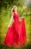 Portrait of young beautiful blonde woman wearing a long red elegant dress posing in a green meadow. Fashionable sexy attractive girl with blue eyes in field. Gorgeous fair hair female, outdoor shot. — Stock Photo