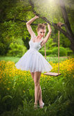 Attractive girl in white short dress posing near a tree swing with a flowery meadow in background. Blonde young woman with ballerina dress under a tree in a ballet position during a bright summer day. — Foto de Stock