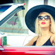 Outdoor summer portrait of stylish blonde vintage woman driving a convertible red retro car. Fashionable attractive fair hair female with black hat in red vehicle. Sunny bright colors, outdoors shot. — Stockfoto #51473557
