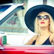 Outdoor summer portrait of stylish blonde vintage woman driving a convertible red retro car. Fashionable attractive fair hair female with black hat in red vehicle. Sunny bright colors, outdoors shot. — ストック写真 #51473557