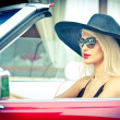 Outdoor summer portrait of stylish blonde vintage woman driving a convertible red retro car. Fashionable attractive fair hair female with black hat in red vehicle. Sunny bright colors, outdoors shot. — Stock Photo #51473559