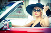 Outdoor summer portrait of stylish blonde vintage woman driving a convertible red retro car. Fashionable attractive fair hair female with black hat in red vehicle. Sunny bright colors, outdoors shot. — Stock Photo