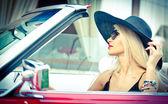 Outdoor Sommer Portrait stilvolle blonde alte Frau Autofahren Cabrio rot retro. modisch attraktive blonde Haare weiblich mit schwarzen Hut in rot Fahrzeug. sonnige helle Farben, im freien gedreht. — Stockfoto
