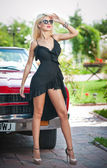 Summer portrait of stylish blonde vintage woman with long legs posing near red retro car. Fashionable attractive fair hair female near a red vintage vehicle. Sunny bright colors, outdoors shot. — Stock Photo