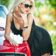 Summer portrait of stylish blonde vintage woman with black sunglasses bent over retro car. Fashionable attractive fair hair female leaning on red vintage vehicle. Sunny bright colors, outdoors shot. — Stockfoto