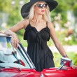 Outdoor summer portrait of stylish blonde vintage woman posing near red retro car. fashionable attractive fair hair female with black hat near a red vehicle. Sunny bright colors, outdoors shot. — Stockfoto