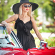 Outdoor summer portrait of stylish blonde vintage woman posing near red retro car. fashionable attractive fair hair female with black hat near a red vehicle. Sunny bright colors, outdoors shot. — Foto de Stock   #51755217