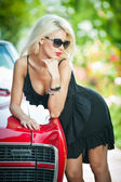 Summer portrait of stylish blonde vintage woman with black sunglasses bent over retro car. Fashionable attractive fair hair female leaning on red vintage vehicle. Sunny bright colors, outdoors shot. — Stock Photo