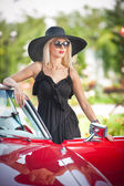 Outdoor summer portrait of stylish blonde vintage woman posing near red retro car. fashionable attractive fair hair female with black hat near a red vehicle. Sunny bright colors, outdoors shot. — Stock Photo