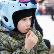 Little girl in ski helmet eats sausage — Stock Photo
