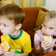 The brother and sister hold crackers and attentively watch TV - Stock Photo