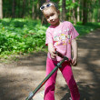Girl with a scooter in the park — Stock Photo