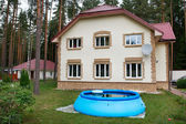 Big house out of town and an inflatable pool — Stock Photo