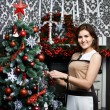 Beautiful young woman near holiday Christmas tree — Photo