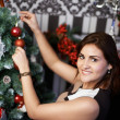 Handsome woman near the holiday Christmas tree — Photo