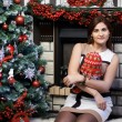 Young woman near Christmas tree and fireplace — Stok fotoğraf