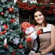 Young woman near Christmas tree and snowman — Foto de Stock