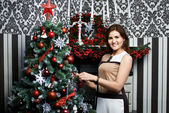 Beautiful young woman near holiday Christmas tree — Stock Photo