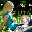 Happy woman and man among flowers — Stock Photo