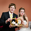 Happy bride and groom with pigeons and rings — Stock Photo