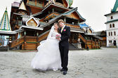 Bride and groom about the wooden palace — Stock Photo