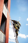 Firefighter climb on fire stairs — Stock Photo