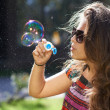 Young girl blows soap bubbles — Stock Photo