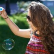 Stock Photo: Young girl blows soap bubbles