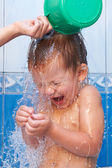 Baby in bathroom pouring water — Stock Photo