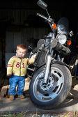 Niño pequeño está parado cerca de moto — Foto de Stock