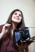 Young girl and old camera — Stock Photo