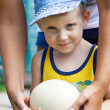 Little boy holding an ostrich eggj — Stock Photo