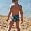 Little boy standing with her back to the beach — Stock Photo