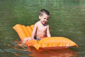 Little boy on mattress on water lake — Stock Photo