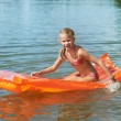 Happy little girl on mattress in lake — Stock Photo