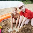 Happy little girls play on sand beach — Stock Photo