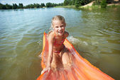Joyful little girl on mattress in lake — Stock Photo