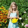 Little girl with watering can near flowers — Stock Photo